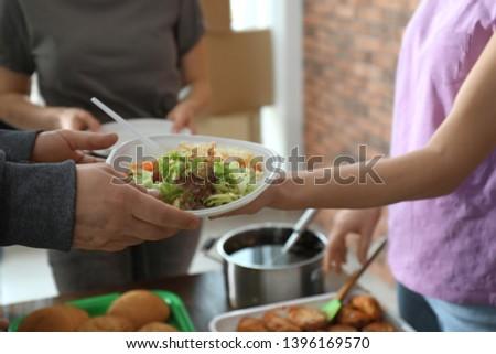 Poor man receiving food from volunteer indoors, closeup #1396169570