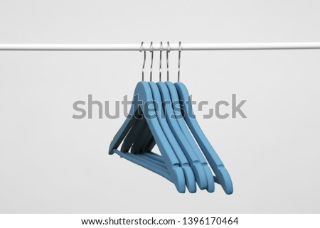 Empty clothes hangers on metal rail against light background #1396170464