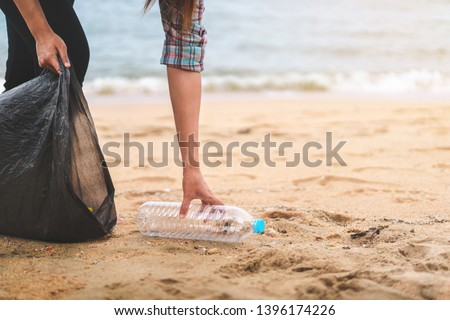 Asian woman picking  bottle into plastic bag black for cleaning the beach in morning time, Volunteer concept. #1396174226