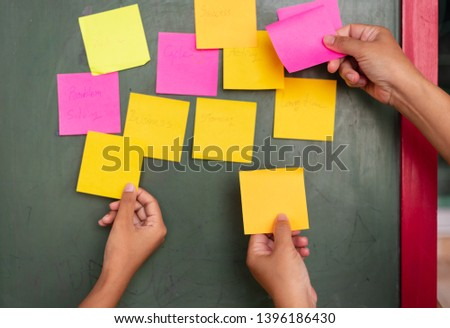 Close up businessman hands holding note sticky for brainstorm ans share idea strategy workshop business.Brainstorming concept. #1396186430