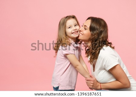 Woman in light clothes have fun with cute child baby girl. Mother, little kid daughter isolated on pastel pink wall background, studio portrait. Mother's Day love family, parenthood childhood concept #1396187651
