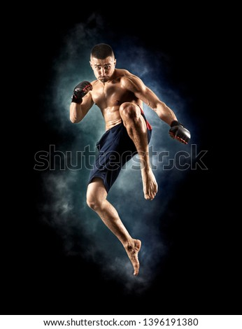 MMA male fighter jumping with a knee kick #1396191380