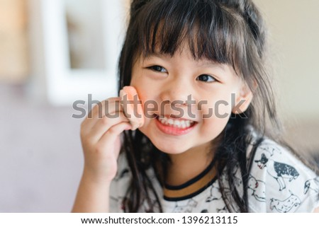 Lovely little asian girl is applying the make up on her cheek with special brush on and looking mirror as she wants to look like her mother.Cute little girl playing with cosmetic at home. #1396213115