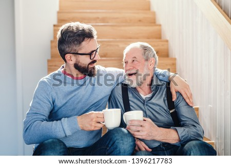 An adult hipster son and senior father sitting on stairs indoors at home, talking. #1396217783