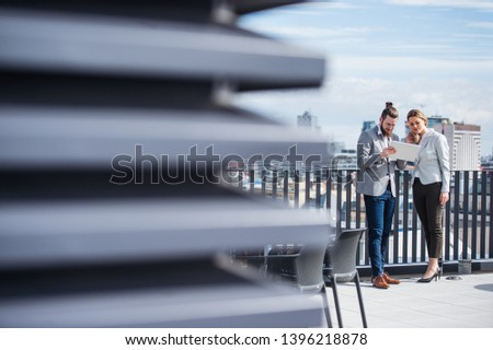 Two young business people with tablet standing on a terrace outside office, working. #1396218878