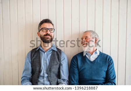 A portrait of adult hipster son and senior father sitting on floor indoors at home. #1396218887