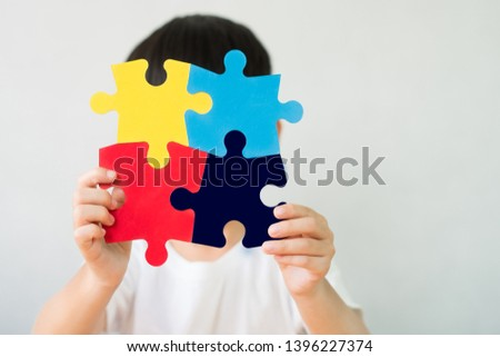 World autism awareness day April 2 - Studio Portrait of a little cute child cover his face with the colorful puzzles pieces. Understand, Autism Spectrum Disorder concept, ASD, Syndrome, Symptoms. #1396227374