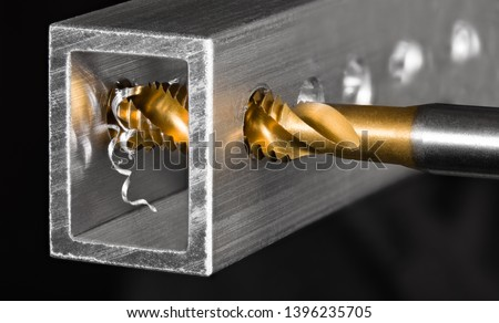 Tapping tool. Steel tap drill coated by titanium. Spiral swarf. Cutting of thread in hole. Aluminum alloy profile. Working cutter. Abstract chip machining detail on black background. Metal production. #1396235705