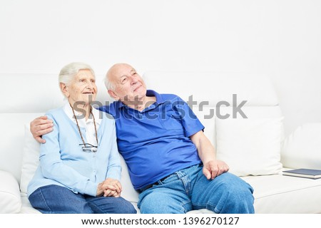 Happy old couple on the sofa enjoys retirement in harmony #1396270127