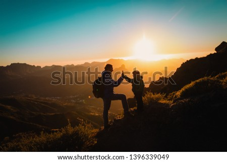 father and little daughter travel in mountains at sunset #1396339049