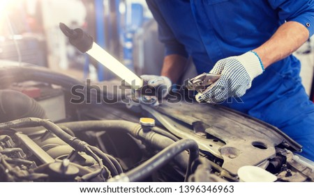 car service, repair, maintenance and people concept - auto mechanic man with lamp and pliers working at workshop #1396346963