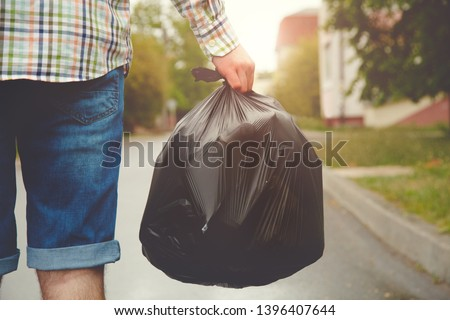 young man taking out garbage in black plastic bag #1396407644