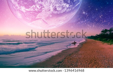 Fantasy landscape of surfer silhouette  walking on the beach of alien planet. Elements of this image furnished by NASA Royalty-Free Stock Photo #1396416968