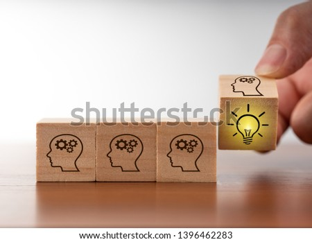 hand that flips one revealing an idea, cubes with head and bulp symbols #1396462283