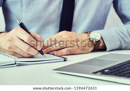 Businessman hand writing note on a notebook. Business man working at office desk. Close up of empty notebook on a blackboard with office supplies. #1396472651