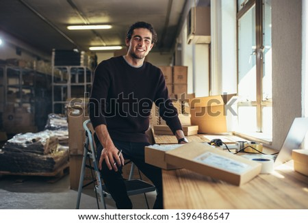 Confident young businessman working at online business store. Small business owner at his work desk. Royalty-Free Stock Photo #1396486547