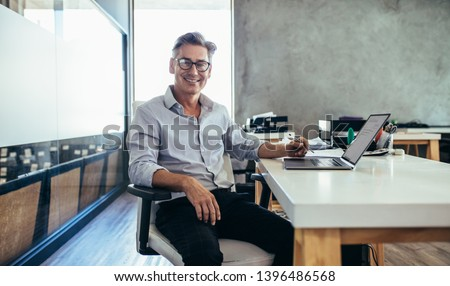 Positive mature businessman sitting at office desk. Mid adult caucasian male executive at work. Royalty-Free Stock Photo #1396486568