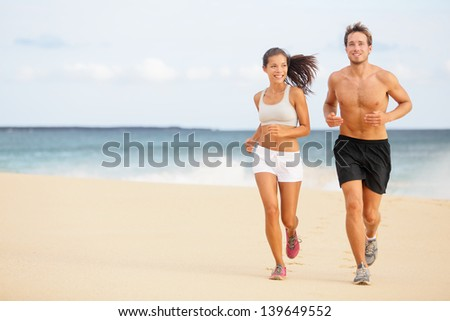 Runners. Young couple running on beach. Athletic attractive people jogging in summer sport shorts enjoying the sun exercising their healthy lifestyle. Multiethnic couple, Asian woman, Caucasian man. #139649552