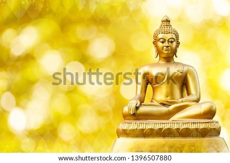 Beautiful of Golden Buddha statue on golden yellow bokeh background.
