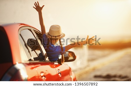 happy child girl goes to summer travel trip in the car