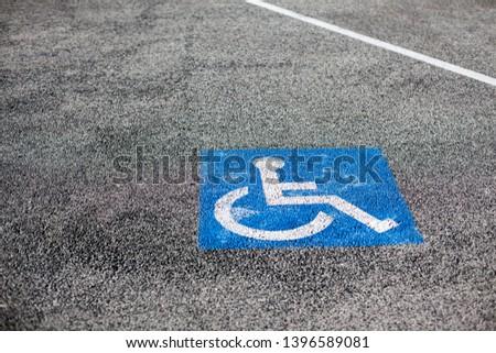 Handicapped parking spot, blue square on asphalt in Cannes Marina, France. Copy space #1396589081