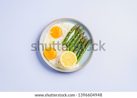 Fried eggs with steamed asparagus flat lay on blue gray background. Delicious healthy lunch. Keto diet #1396604948