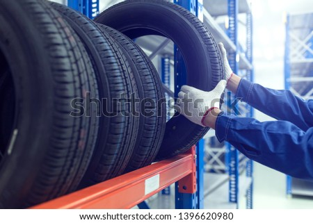 Large modern warehouse with forklifts and stack of car tires #1396620980