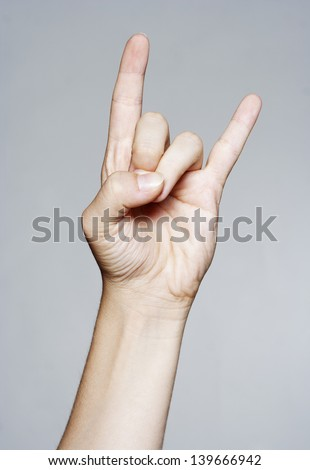Hand giving the devil horns gesture Royalty-Free Stock Photo #139666942