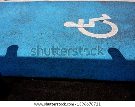disabled icon sign in white in centre of protected zone in blue paint #1396678721