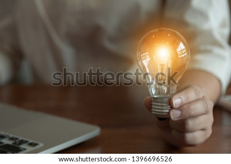 woman hands holding light bulb in working place. #1396696526
