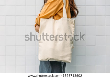 Woman is holding tote bag canvas fabric for mockup blank template. Royalty-Free Stock Photo #1396713602