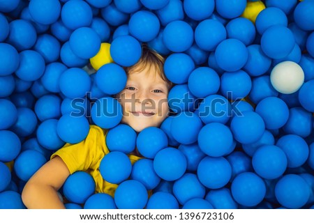 Child playing in ball pit. Colorful toys for kids. Kindergarten or preschool play room. Toddler kid at day care indoor playground. Balls pool for children. Birthday party for active preschooler #1396723106