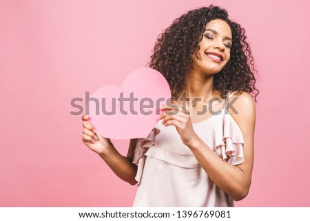 Portrait of attractive happy smiling american afro woman isolated against pink background with big pink heart. #1396769081