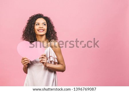 Portrait of attractive happy smiling american afro woman isolated against pink background with big pink heart. #1396769087