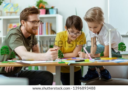 Creating informative poster. Concentrated little boys being interested in drawing project while visiting ecology classes #1396893488
