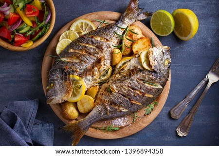 Roasted fish and potatoes, served on wooden tray. overhead, horizontal - image Royalty-Free Stock Photo #1396894358