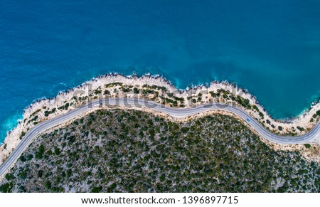 Aerial landscape of coastline and a road seascape. Car drives down the empty asphalt road running along the sunny Mediterranean shoreline of Turkey. Tourist car cruises down the scenic coastal road . #1396897715