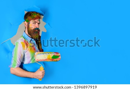 Repair. Painter with painting roller through hole in paper. Professional painter in dirty shirt making hole in paper wall. Serious painter man. Handsome bearded worker with paint roller. Copy space. #1396897919