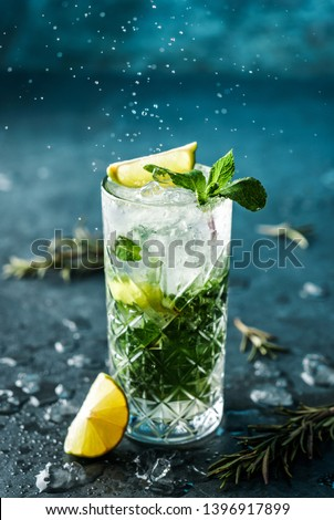 Fresh Mojito cocktail with lime, rosemary, mint and ice in jar glass on dark blue background. Studio shot of drink in freeze motion, drops in liquid splash. Summer cold drink and cocktail #1396917899