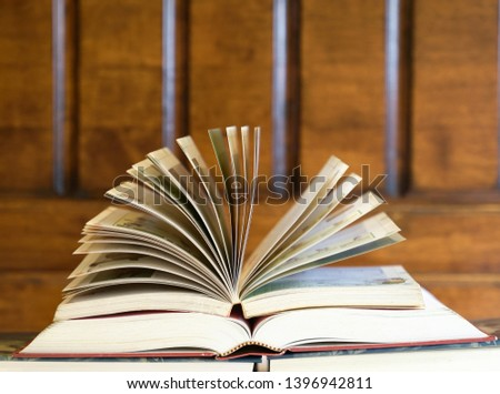 Open textbook on top of books with wood background, an education concept #1396942811