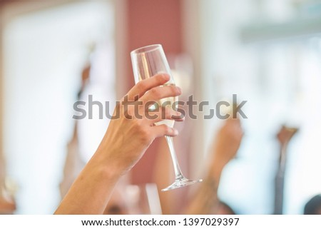 Glass of champagne on the background of friends at a party. #1397029397