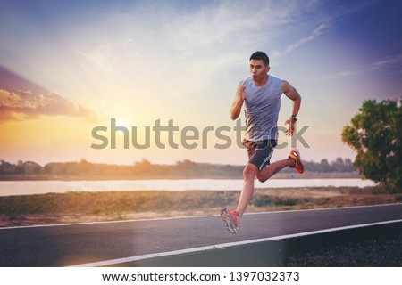 Silhouette of man running sprinting on road. Fit male fitness runner during outdoor workout with sunset background #1397032373