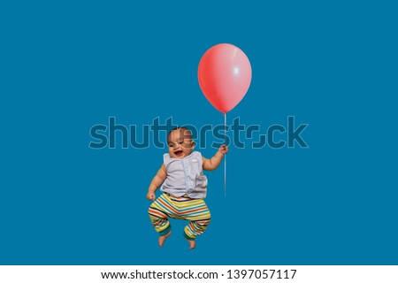 Happy Baby flying holding air balloon  on blue background