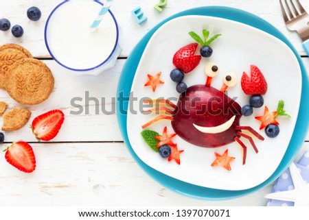 Fun Food for kids. Cute smiling crab made of fresh fruits - apple, strawberry, blueberries and fresh mint - for a healthy breakfast with milk and biscuits #1397070071