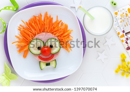 Fun food for kids - cute smiling clown face on ham sandwich decorated with fresh cucumber, carrots and tomatoes for a healthy lunch for children. Creative cooking idea #1397070074