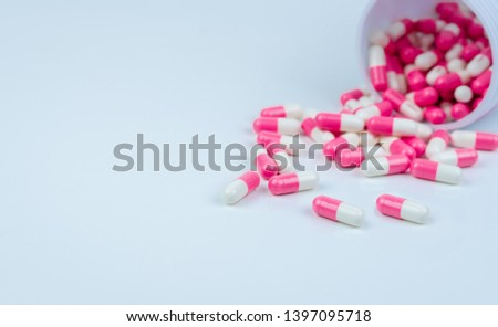 Pink-white capsule pills spread out of drug bottle. Antipsychotic drug. Capsule medicine for treatment depression. Anti-anxiety drug. Global healthcare. Pharmacy background. Pharmaceutical industry. #1397095718
