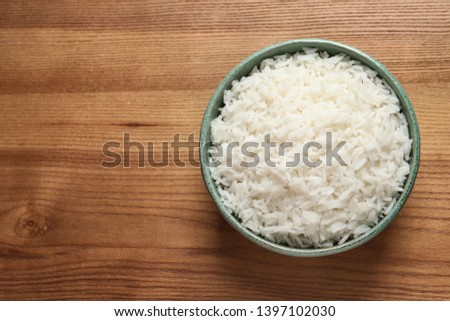 Bowl of tasty cooked rice on wooden background, top view. Space for text #1397102030
