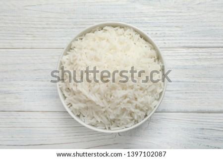 Bowl of tasty cooked rice on white wooden background, top view #1397102087