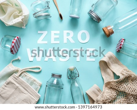 Zero waste concept. Textile eco bags, glass jars and bamboo toothbrush on blue background with Zero Waste white paper text in center. Eco friendly and reuse concept. Top view or flat lay #1397164973