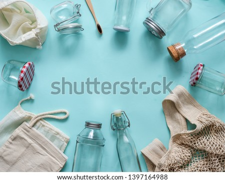 Zero waste concept. Textile eco bags, glass jars and bamboo toothbrush on blue background with copy space for text in center. Eco friendly and reuse concept. Top view or flat lay Royalty-Free Stock Photo #1397164988